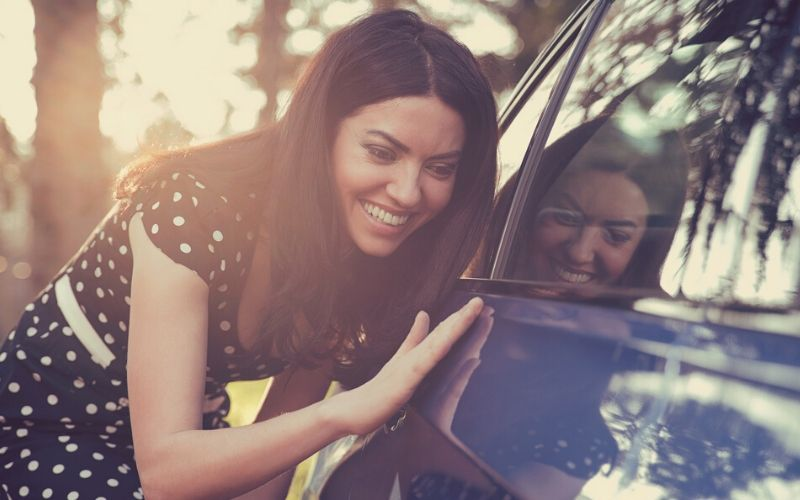 excited young woman and her new car